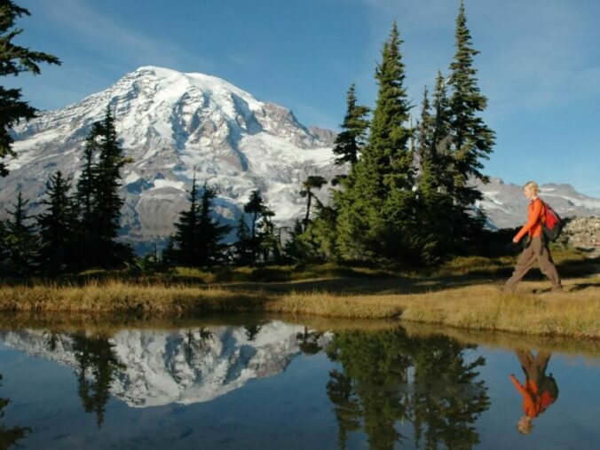 a young woman hikes by a small pond in front of mt. rainier, washington state