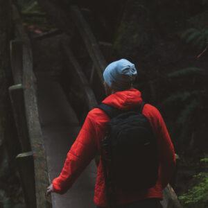 Man in red sweatshirt walking across wood bridge