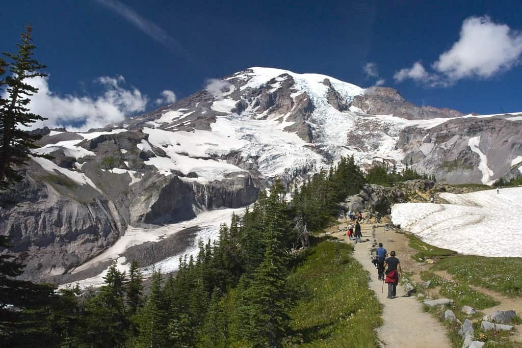 Small group of people walking on a hiking path towards a snow covered mountain in the distance