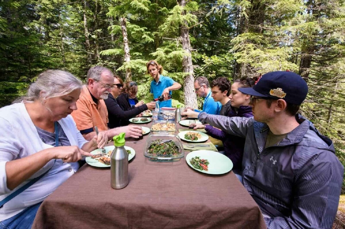 9 people sitting and eating at a picnic table surrounded by evergreen trees on a group trip