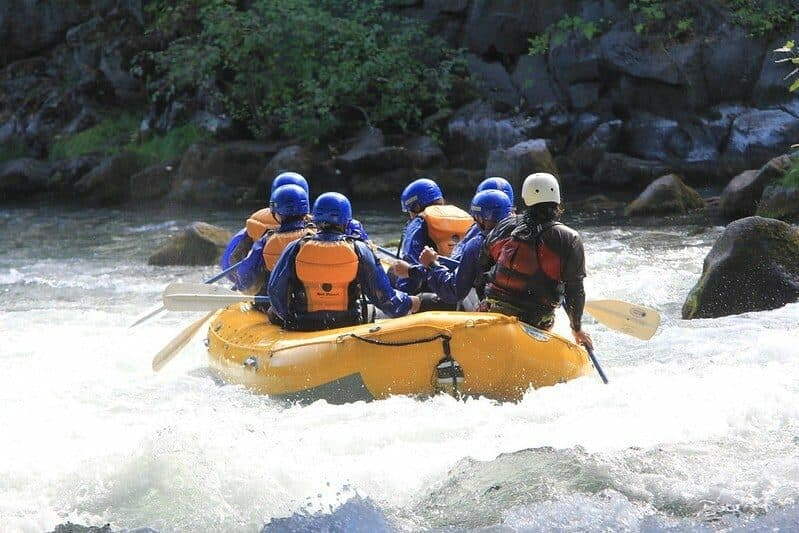 7 people in a yellow raft on small white rapids, all wearing white water rafting