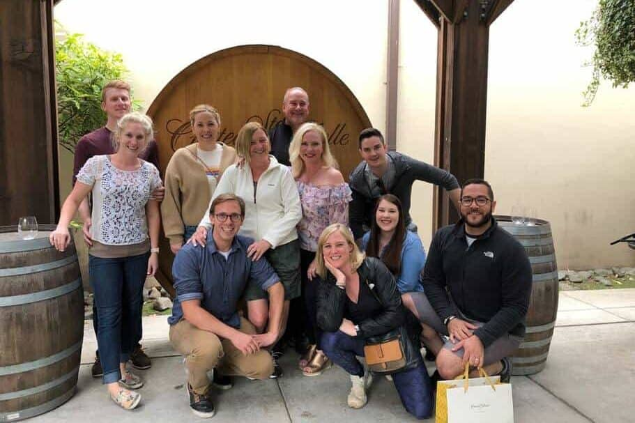 11 people standing and kneeling in front of tall wine barrel during a company wine tasting tour