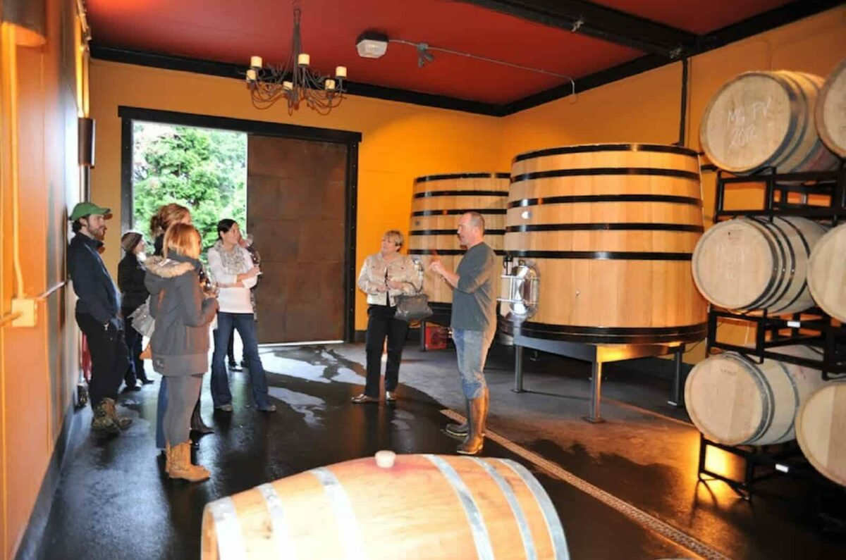 4 people standing and listening to 1 person talking inside a room with several huge wine barrels